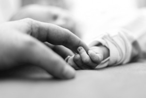 newborn holding mother's hand