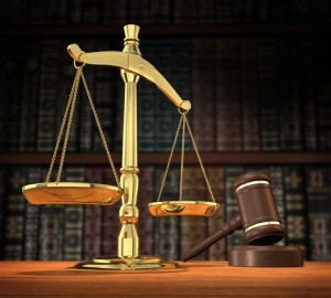 Scales of justice and gavel on desk with dark background that allows for copyspace. court